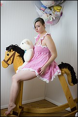 Kimmie in a pink dress on an ABDL rocking horse